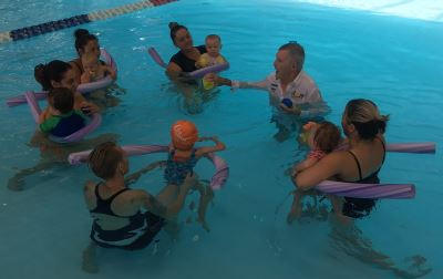 Laurie Lawrence in the water with mums and babies during an infant aquatics class