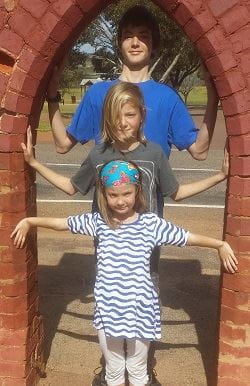 Jewel with her two brothers standing under an arch