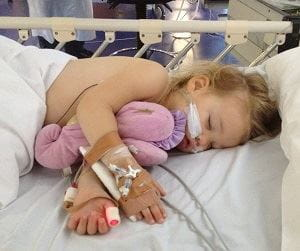Jewel laying in a hospital bed with tubes attached to her