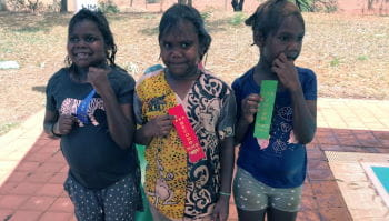 Three aboriginal girls with their swimming place ribbons