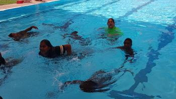 Aboriginal children enjoying swimming lessons at Jigalong Pool with Pool Manager David Lucas