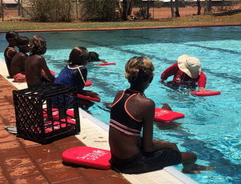 Aboriginal children sitting along the edge of a pool watching their instructor demonstrate freestyle in the water