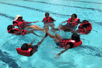 A group of aboriginal children int he water with their swim instructor, floating on their back while wearing lifejackets