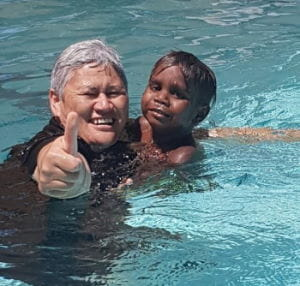 An adult and aboriginal child swimming together in the Jigalong pool
