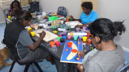 A group of indigenous women completing dot paintings at the Jigalong Shed