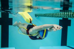A girl swimming underwater while towing a rescue tube
