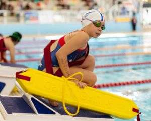 A girl wearing goggles and a swim cap, holding a rescue tube while kneeling on the starting blocks by the pool