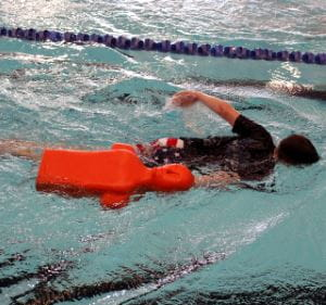 A boy swimming with a rescue manikin in the pool at HBF Stadium