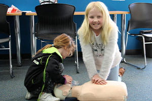 Two young girls practising CPR on a manikin