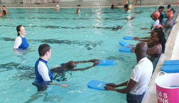 Kenyan adults in the pool with their swim instructor at Belmont Oasis