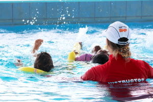 An instructor with children swimming in the pool