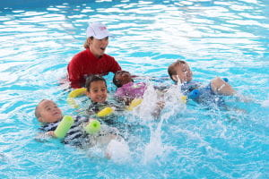 Children kicking on their back with pool noodles and their instructor