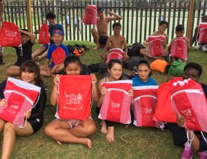 Multicultural students with their red Swim and Survive packs at Lynwood Senior High School
