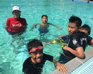 Multicultural boys with their swim instructor in the pool at Lynwood