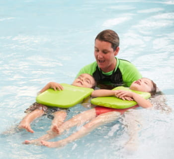 A swim instructor helping two children to float on their back with green kickboards