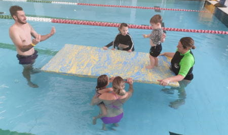 Parents and children in the water with their babies and a swim instructor, with a child walking across a foam mat
