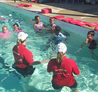 Two swimming instructors in the water with muticultural children doing a swimming lesson