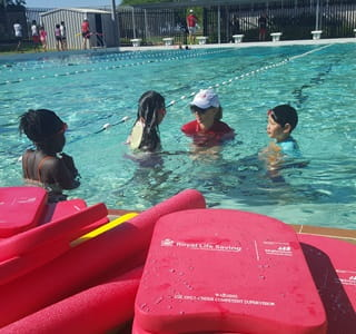 Swimming instructor in the water with three girls doing a swimming lesson