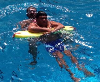 Two lifeguards in the pool in Oman practising rescues using a rescue tube