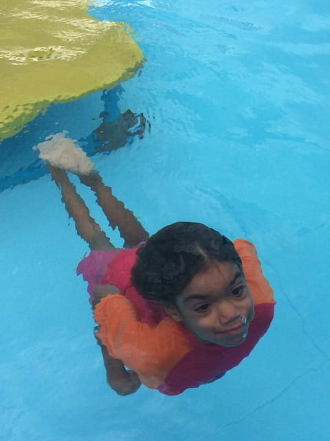 young aboriginal girl swimming up from bottom of swimming pool