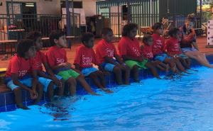 Aboriginal children sitting along the edge of the swimming pool at Newman Aquatic Centre