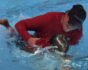 A swim instructor helping an Aboriginal children learn to swim in a pool