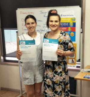 Two Newman parents with their heart Beat Club certificates