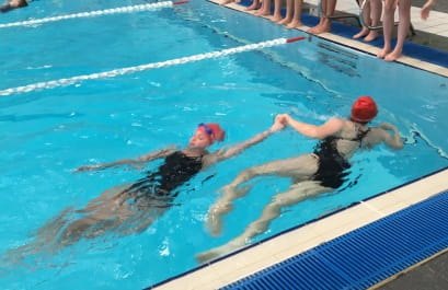 two students competing in a tow swimming race at HBF stadium