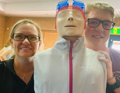 Swim school coordinator Tracye Sykes with an AUSTSWIM course candidate standing with a resuscitation Anne doll