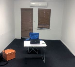 An empty office with just a plastic table and camping chair