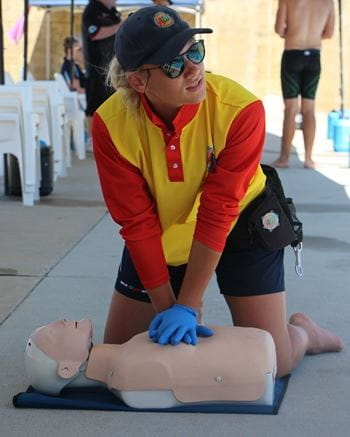 A team member from Adventure World performing CPR on a manikin