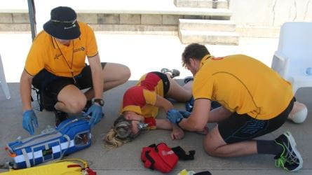 Two lifeguards attending to a person passed out on the ground
