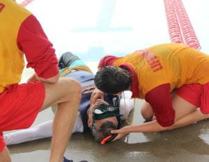 A lifeguard checking a man who has just been pulled from the water
