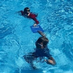 Two Aboriginal boys using a kickboard to perform a tow rescue in the pool