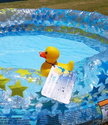 A rubber duck with the Don't Duck Out promotional message tied to it, sitting on the edge of a portable paddle pool