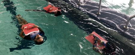 Three multicultural girls in the water floating on their backs with kickboards