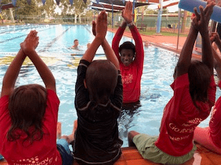 Martu children practising 'rocket arms' with their instructor in the pool at Newman