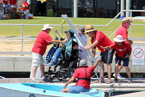 Assisting sailability participant getting on a boat