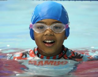 a child wearing goggles smiling at the camera while in the water