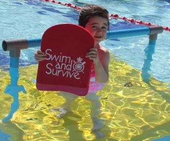 A young girl in the pool holding a Swim and Survive kickboard