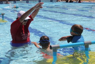 A swim instructor with two children in the water at Gingin