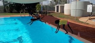 Aboriginal children diving into the pool at Yaneyarra