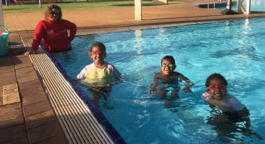 three children in pool with swim instructor