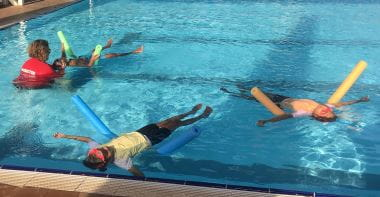 three children floating on their backs using pool noodles with swim instructor assisting