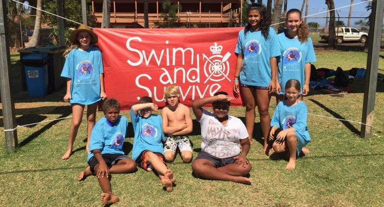 A group of aboriginal children in front of the red Swim and Survive banner at the Spirit Carnival