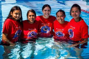 Five aboriginal young women in the pool with red Spirit Carnival t-shirts on