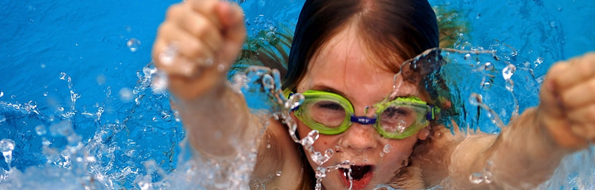A young girl burst out of a swimming pool