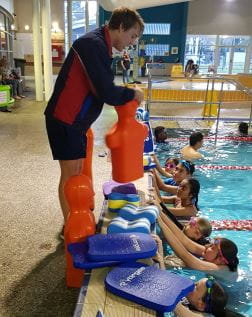 A lifeguard trainer holding a tow manikin by the pool with kids in the water
