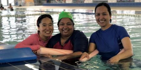 Three multicultural women in the pool with pool noodles, smiling