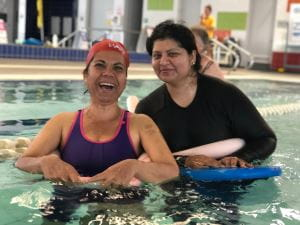 Two multicultural women in the pool with kickboards and smiling